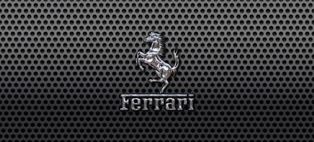 Ferrari Prancing Horse of Maranello logo on a black metal mesh wallpaper 1440x900